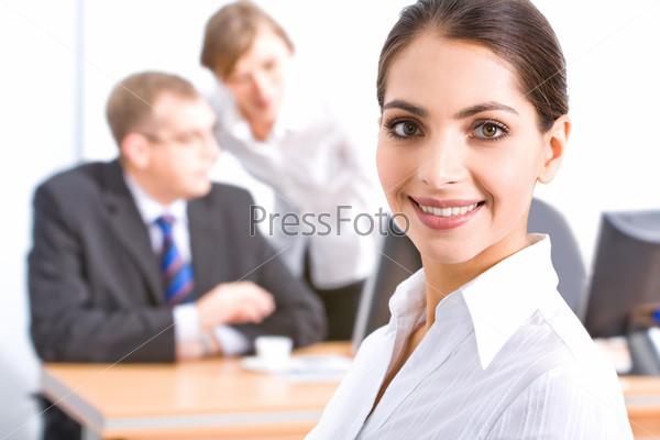Лицо красивой сотрудницы с карими глазами на фоне ее коллег