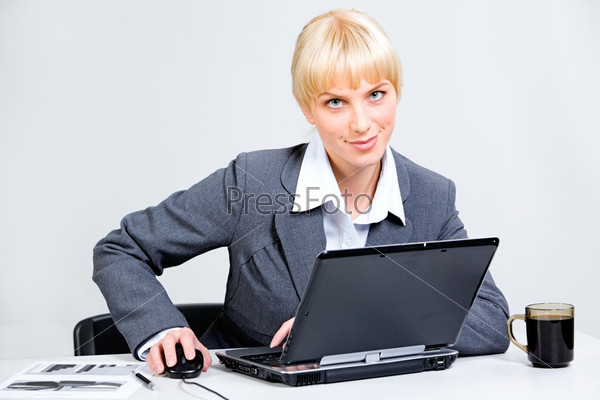 Attractive business woman sitting at the table with a laptop on it touching her hand on mouse