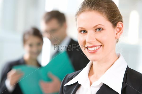 Портрет молодой улыбающейся деловой женщины на фоне бизнес-группы