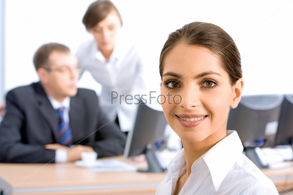 Portrait of successful young woman on the background of two businesspeople in the office