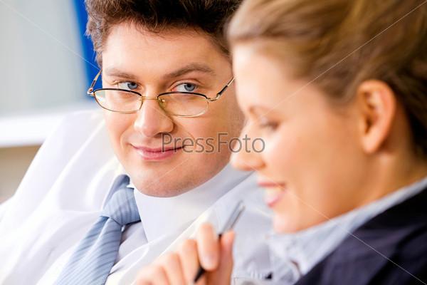 Бизнесмен в очках смотрит на свою коллегу во время обсуждения работы