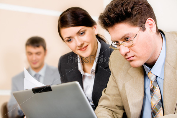 Successful business man and woman looking at the laptop in a working environment