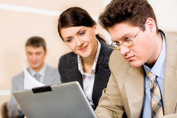 Успешный бизнесмен и деловая женщина смотрят на экран ноутбука в рабочей обстановке