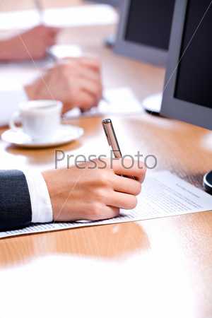 Vertical image of hand holding a pen in a working environment