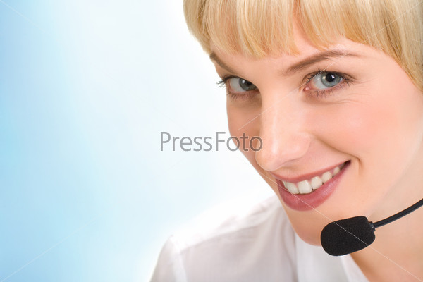 Face of beautiful telephone operator with headset isolated on a blue background