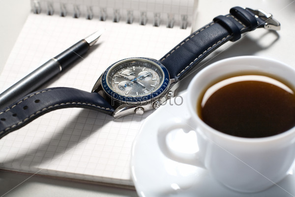 Image of watch and pen over notebook with cup of coffee near by