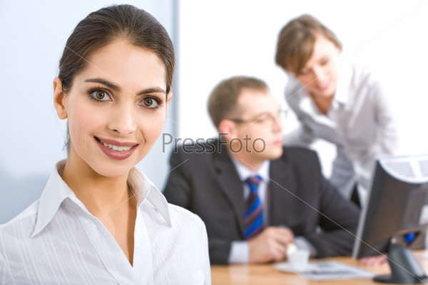 Portrait of strong woman with charming smile on the background of business people