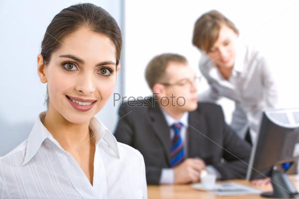 Портрет сильной женщины с очаровательной улыбкой на фоне деловых людей