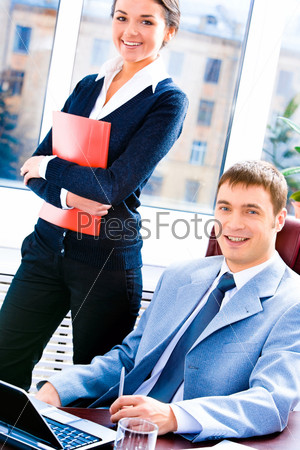 Portrait of business woman standing and man sitting at the table near by