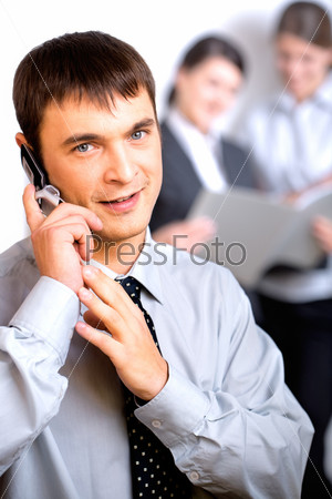 Successful business man calling on cellphone on the background of women