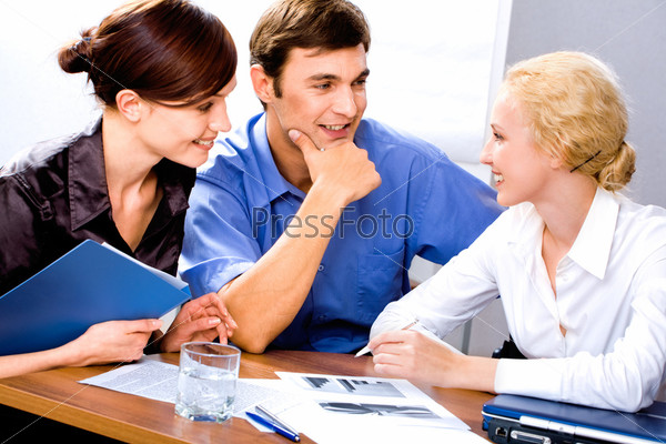 Group of three successful business people discuss working ideas