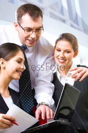 портрет деловых людей, склонившихся над ноутбуком во время важной встречи
