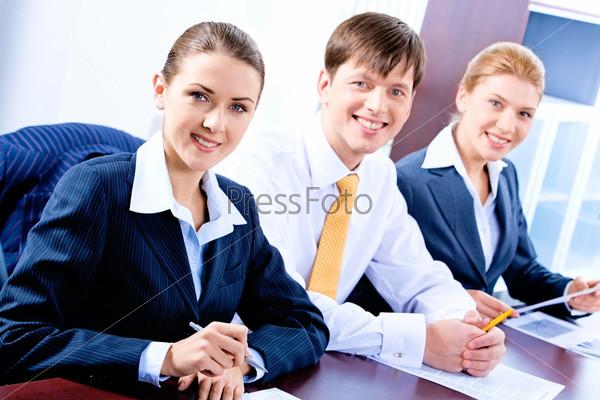 Трое успешных деловых людей сидят за столом в ряд и смсотрят в камеру с улыбкой