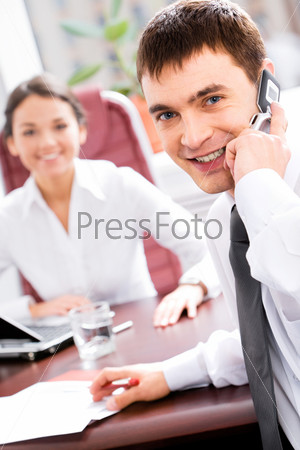 Business man calling on cellphone while conversation with colleague