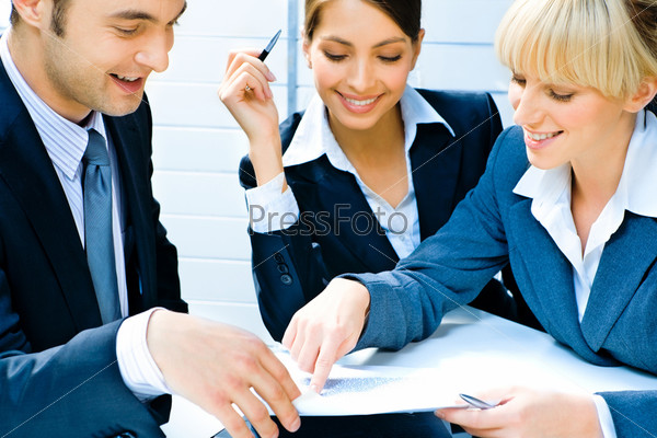 Business woman demonstrating her plan of work to co-workers pointing at a document