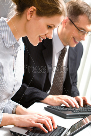 Row of business people typing something over laptop and computer