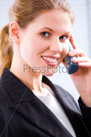 up of a young attractive businesswoman speaking on the phone looking at camera with smile