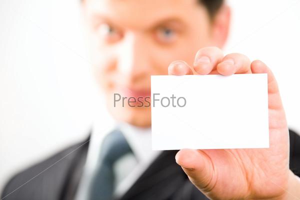 Визитная карточка в руке бизнесмена крупным планом на фоне его лица