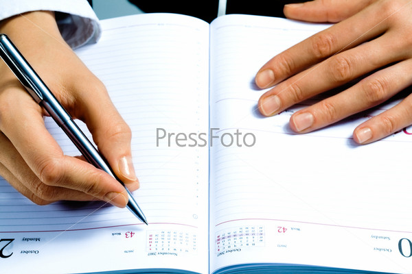 Image of writing instrument in human hands over notepad