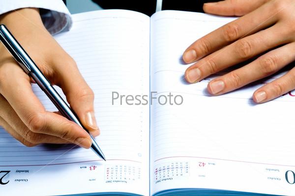 Руки человека, держащего ручку над блокнотом
