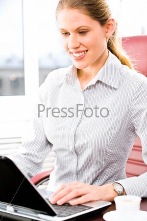 Фотография на тему Молодая деловая женщина сидит за столом в офисе и смотрит на экран ноутбука