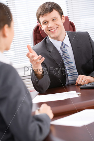 Portrait of boss sitting at the table and telling his business idea to colleague
