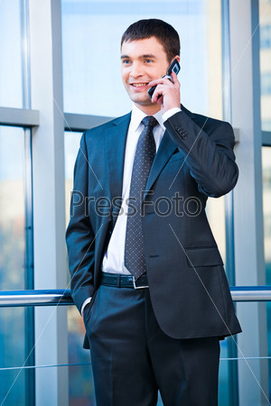 Portrait of confident business man calling on the mobile in the office