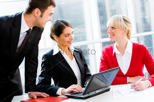 Portrait of business people looking at woman at working meeting