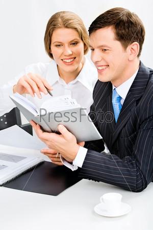 портрет деловых людей, планирующих свой рабочий график, смотря в блокнот вместе
