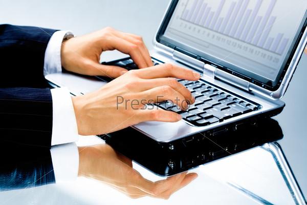 Человеческая рука, набирающая деловой документ на ноутбуке