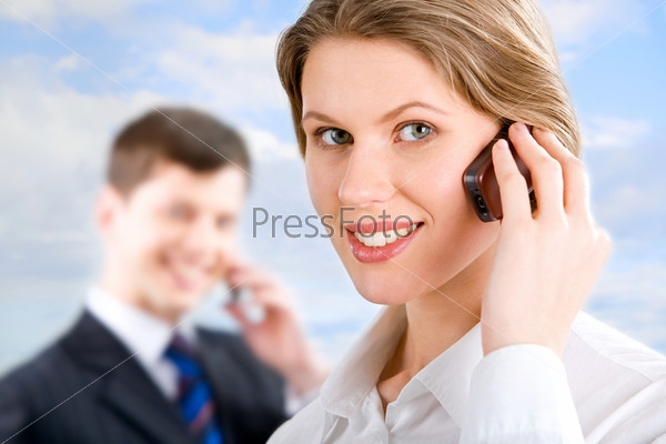 Image of telephone conversation of attractive woman and businessman