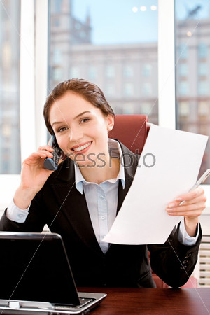 Portrait of strong woman sitting at the table and speaking with somebody by cellphone