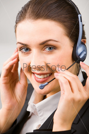 Portrait of beautiful customer service representative touching her headset