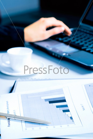 Image of pen with document lying on the table in a working environment