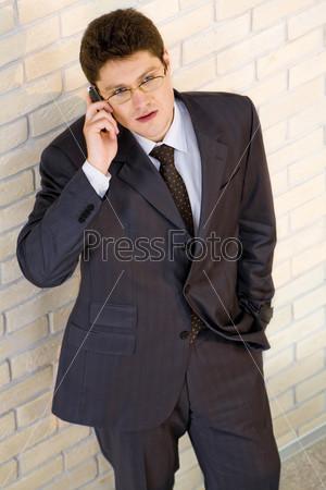Бизнесмен, стоящий на флне кирпичной стены и разговаривающий по телефону