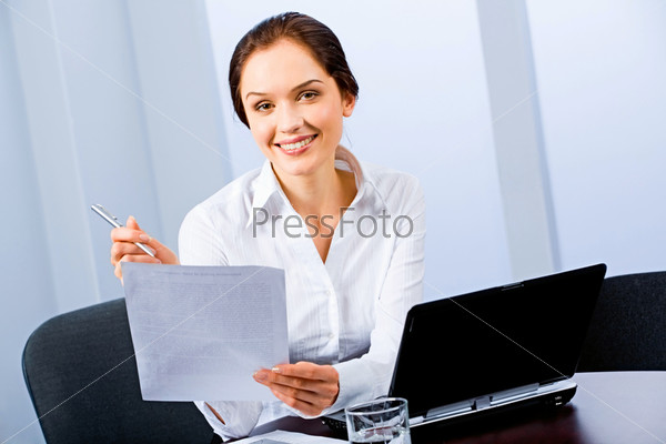 Portrait of beautiful secretary sitting at the table and holding a paper, pen