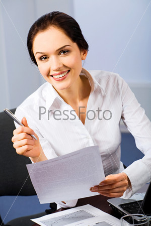 Portrait of beautiful receptionist holding a paper and pen on a blue background