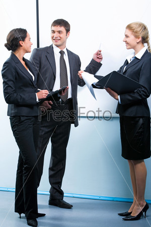 Successful businessman explaining business plan to one of his colleagues pointing at a board