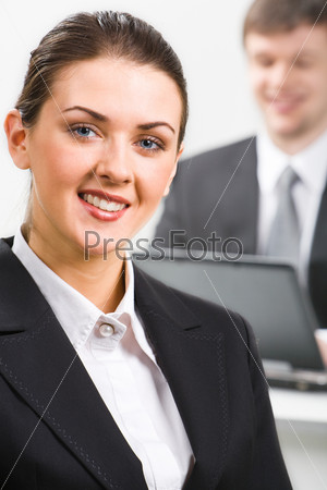 Portrait of confident woman in suit on the background of man