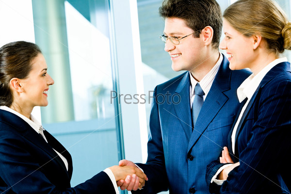 Business man and woman shaking hands making an agreement at meeting
