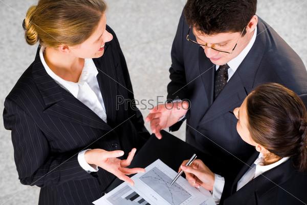 Фотография на тему Трое успешных людей обсуждают деловой проект на встрече