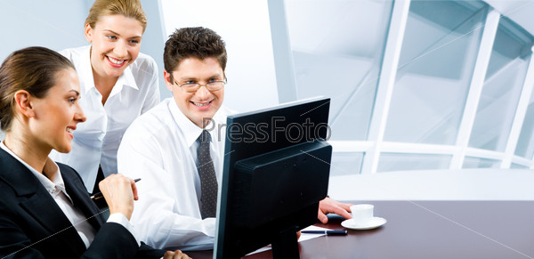 Team of three business people looking at monitor of computer in the office