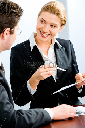 Business woman telling about work to her colleague in the office