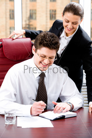 Image of confident boss ready to write a text with secretary standing near by