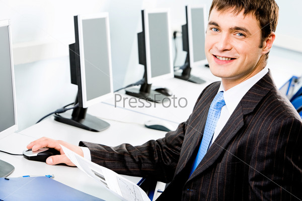 Portrait of handsome business man sitting at the table and touching a computer mouse in the classroom