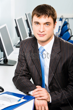 Portrait of confident young teacher looking at camera in the classroom