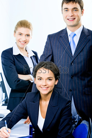 Portrait of group of three successful business people looking at camera and smiling