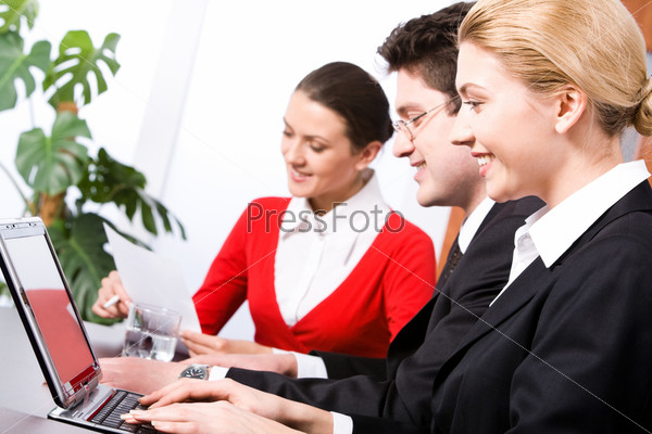 Row of three business people sitting at the table and working