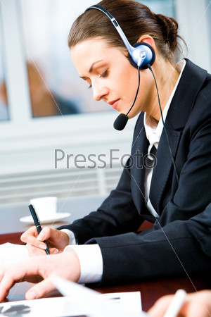 Portrait of telephone operator with headset writing something in the office
