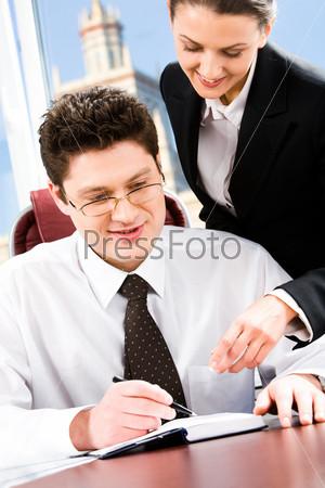 Портрет двух деловых людей в офисе, указывающих на что-то в записной книжке